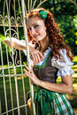 Romantic bavarian girl in the garden wearing dirndl standing near cage Royalty Free Stock Photo