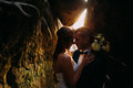Romantic beautiful bride and elegant stylish groom holding each other in darkened rock cleft backgrounded by sunset shining Royalty Free Stock Photo