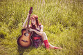Romantic beautiful girl holding her guitar travelling with summer hippie style Stock Photo