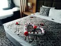 Romantic bed decorated with flowers as a heart large with pillows Stock Image