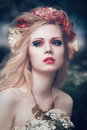 Romantic blond woman art fashion portrait of young girl with flowers in hair on meadow Stock Image