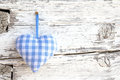 Romantic blue/white checkered heart shape hanging above white wooden surface on a nail- white wooden shabby chic background for Royalty Free Stock Photo