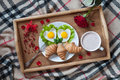 Romantic breakfast in bed with heart-shaped eggs, jam toasts, croissants, rose flower and petals Royalty Free Stock Photo