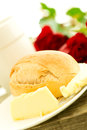 Romantic breakfast with flowers angle view bread butter and roses on wooden table composition Royalty Free Stock Photography