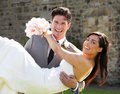 Romantic bride and groom embracing outdoors smiling to camera Royalty Free Stock Images