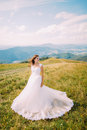 Romantic bride posing on the green and yellow field with small flowers. Hill landscape at background Royalty Free Stock Photo