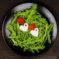 Romantic Caprese salad with mozzarella, cut as hearts, tomatoes and green basil, black plate, dark background. Top view Royalty Free Stock Photo