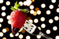 Romantic chocolate dipped strawberry on a fork silver ready to be eaten out of focus yellow lights background Stock Image