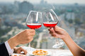 Romantic clicking hands holding glasses of red wine and on the foreground Stock Images