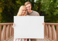Romantic couple with blank white board summer holidays love travel tourism relationship and advertisement concept on the bridge Stock Image