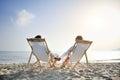 Romantic couple on deckchair relaxing enjoying sunset on the beach