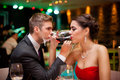 Romantic couple drinking wine with crossed arms Royalty Free Stock Photography