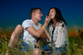 Romantic couple eating red raspberry, sit on grass at sunset on outdoor, dark night sky, love concept, young adult people