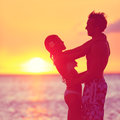 Romantic couple embracing kissing on beach sunset at two young lovers playful and happy together honeymoon travel holiday Royalty Free Stock Photos
