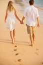 Romantic couple holding hands walking on beach at sunset man and women in love footprints in the sand Royalty Free Stock Photo