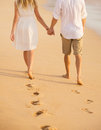 Romantic couple holding hands walking on beach at sunset man and women in love footprints in the sand Stock Images