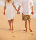 Romantic couple holding hands walking on beach at sunset man and women in love footprints in the sand Royalty Free Stock Photos