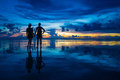 Romantic couple holding hands watching the sunset on the beach Royalty Free Stock Photo