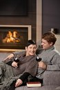 Romantic couple at home young sitting on sofa in front of fireplace drinking red wine Stock Photography
