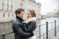 Romantic couple in jackets embracing by railing side view of young Stock Image