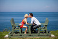 Romantic couple kissing on the bench in vacation Stock Images