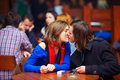 Romantic couple kissing in crowded cafe indoor Stock Photography