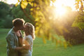 Romantic couple kissing each other at sunset in a park Royalty Free Stock Photo