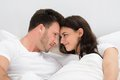 Romantic couple looking at each other lying on bed Royalty Free Stock Photography