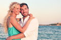 Romantic couple in love enjoying sunset at beach young happy women and men lovers embracing and hugging romance on summer Stock Photo