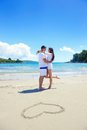 Romantic couple in love have fun on the beach with heart drawi Royalty Free Stock Photo