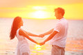 Romantic couple lovers holding hands beach sunset at happy multiethnic young in love having romance and fun together during Stock Photography