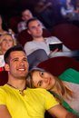 Romantic couple at movie theater young sitting in cinema watching smiling Stock Photos