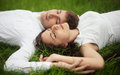 Romantic couple outdoor relaxing on grass Stock Images