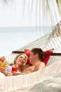Romantic couple relaxing in beach hammock smiling Stock Photos