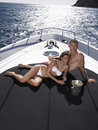 Romantic couple relaxing on yacht with champagne flutes looking away while Stock Image