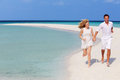 Romantic couple running on beautiful tropical beach holding hands Royalty Free Stock Image