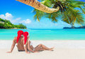Romantic couple in Santa hats tanning at island palm beach Royalty Free Stock Photo
