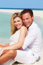 Romantic couple sitting on beautiful tropical beach smiling Stock Photo