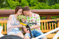 Romantic couple sitting on a bench and smelling flowers in a par Royalty Free Stock Photo