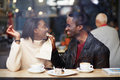 Romantic couple spends time together in the cafe portrait of young love at a coffee shop boyfriend wiping her mouth with a napkin Royalty Free Stock Images
