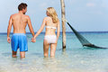 Romantic couple standing in beautiful tropical sea holding hands Stock Photography