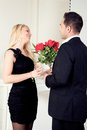 Romantic couple standing in evening attire in front of a fireplace with a vase of red roses talking and looking into each others Stock Photos