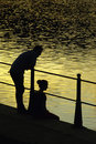 Romantic couple at sunset riverside s silhouettes Royalty Free Stock Photos