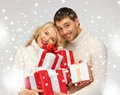 Romantic couple in a sweaters with gift boxes picture of Royalty Free Stock Photos