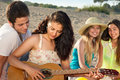 Romantic couple and two female friends at the beach young playing guitar Royalty Free Stock Image