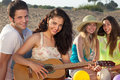 Romantic couple and two female friends on the beach young sitting playing guitar Royalty Free Stock Photography