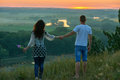 Romantic couple walk on hill at sunset on country outdoor, girl with bouquet of wild flower, beautiful landscape and bright yellow Royalty Free Stock Photo