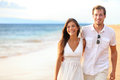 Romantic couple walking on beach honeymoon travel vacation summer holidays romance young happy lovers asian women and caucasian Stock Image