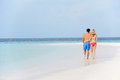 Romantic couple walking on beautiful tropical beach in the sun Stock Photos