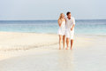 Romantic couple walking on beautiful tropical beach towards camera Royalty Free Stock Images